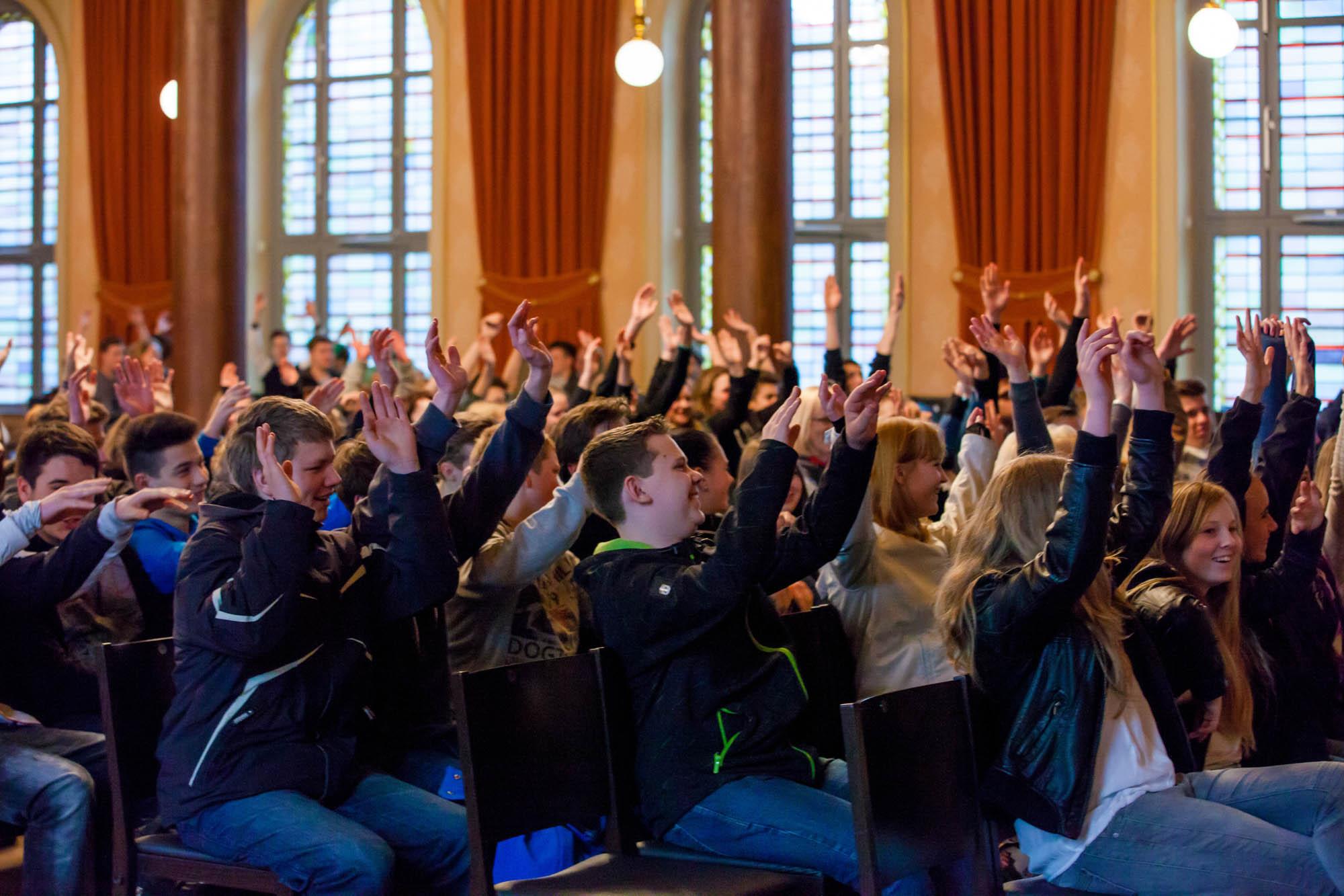 Schüler heben die Hand und machen bei einem Vortrag mit