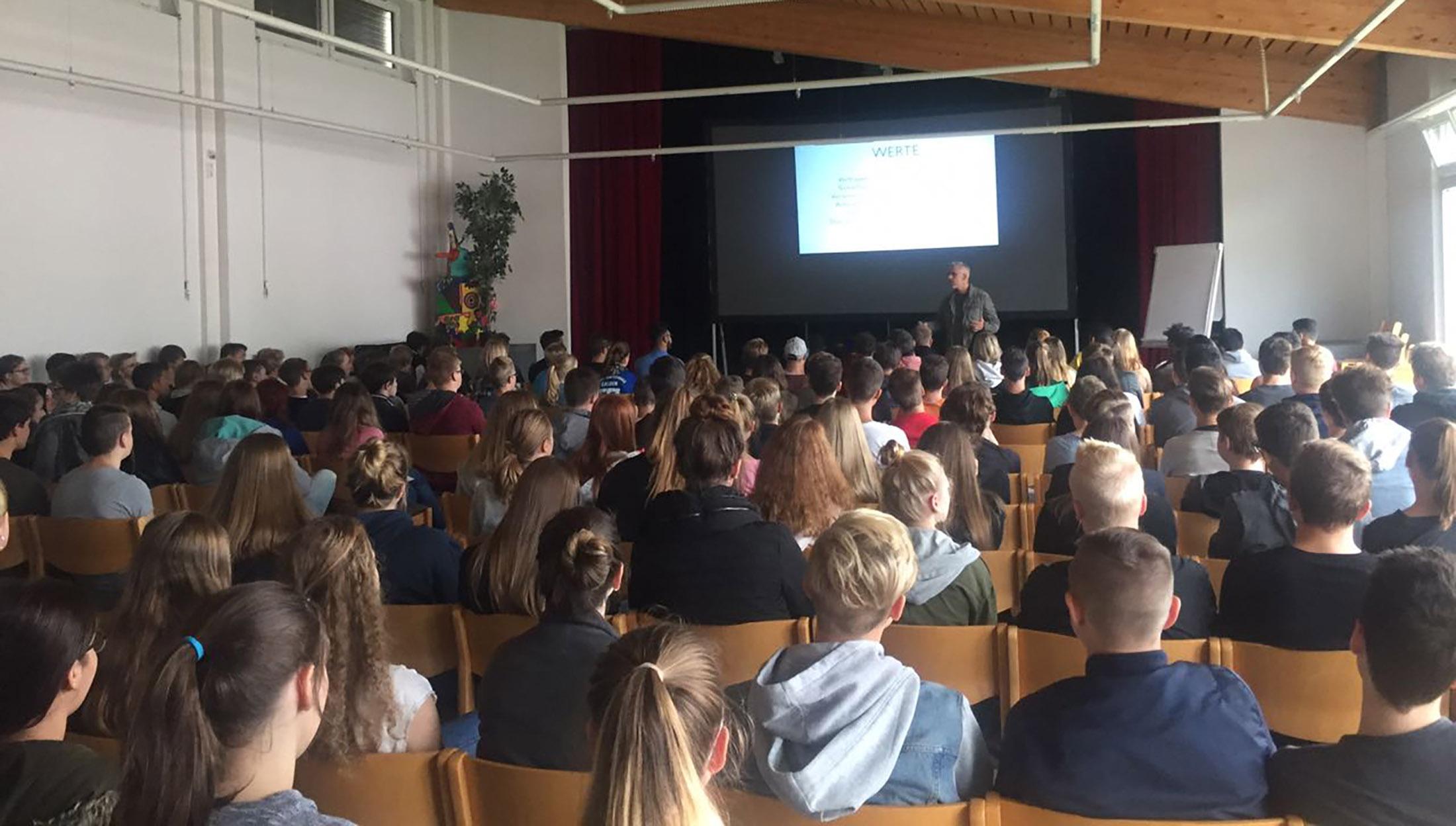 Key Note Speaker und Vortragsredner auf der Bühne und im Vordergrund sind Schüler