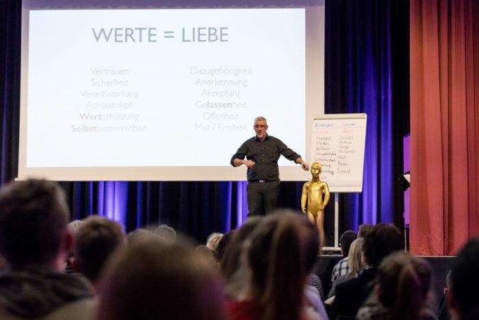 Key Note Speaker und Vortragsredner auf der Bühne und im Vordergrund sind Erwachsene