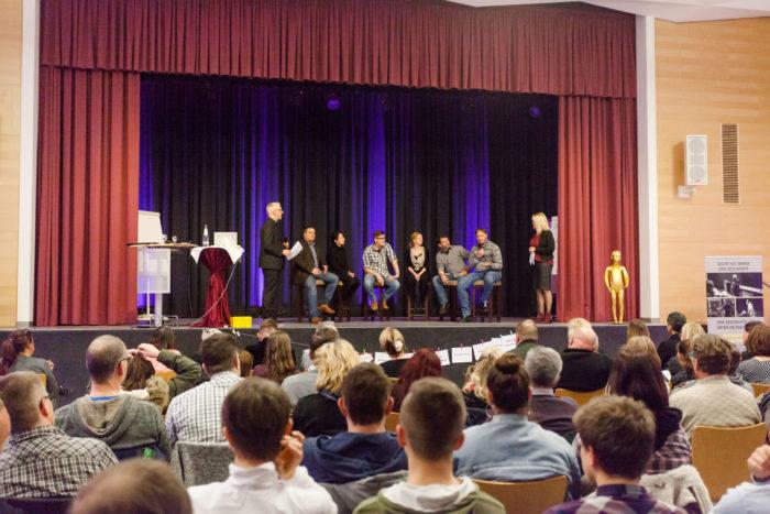 Key Note Speaker und Vortragsredner auf der Bühne im Vordergrund Erwachsene