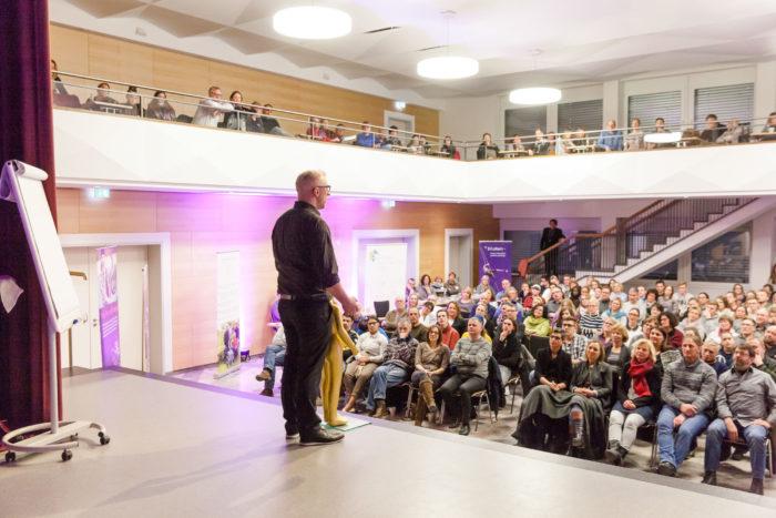 Key Note Speaker und Vortragsredner auf der Bühne und im Hintergrund sind Erwachsene