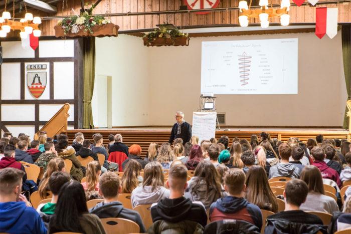 Key Note Speaker und Vortragsredner vor der Bühne und im Vordergrund sind Schüler