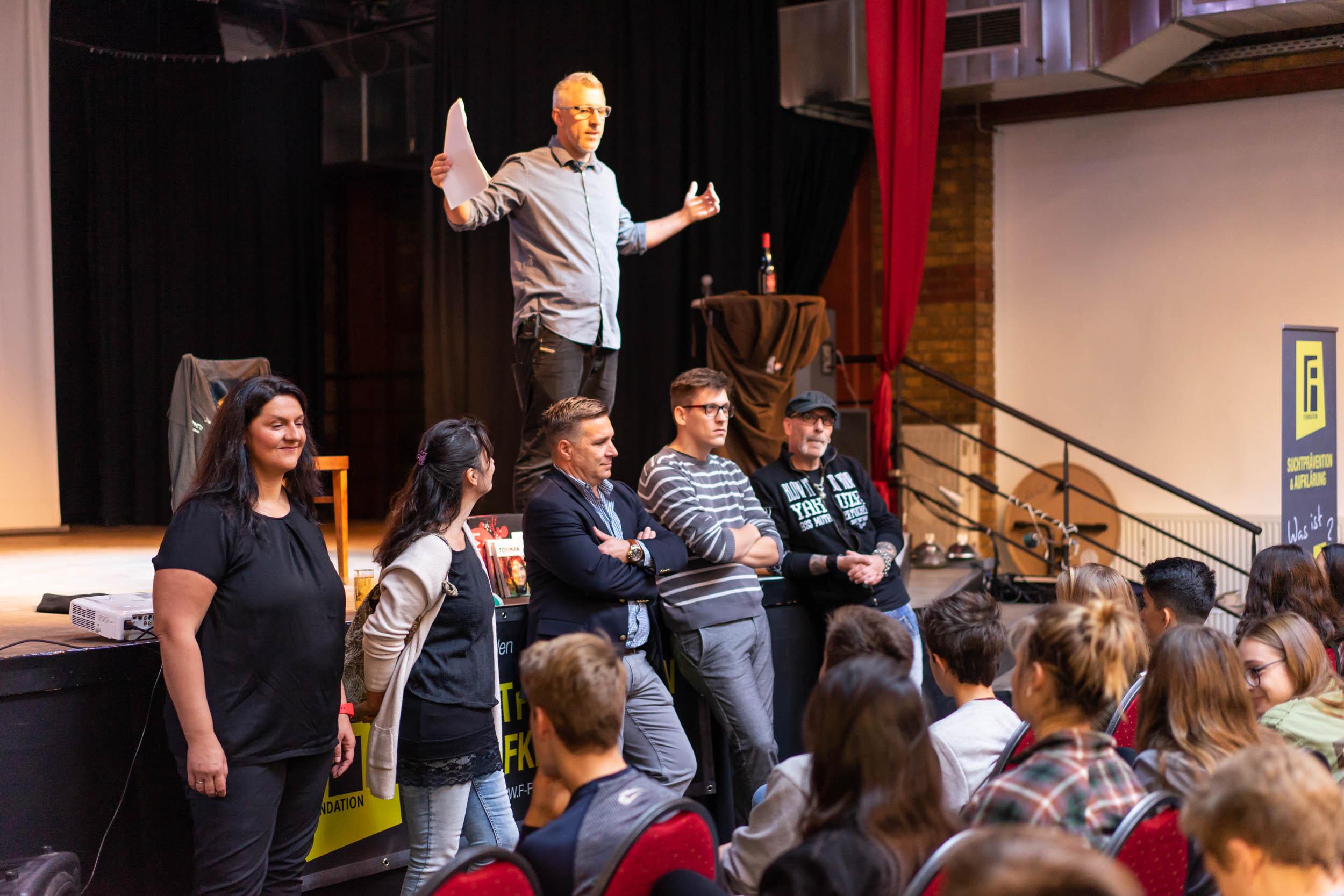 Key Note Speaker und Vortragsredner auf der Bühne und im Vordergrund sind Kollegen und Schüler