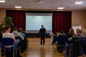 Key Note Speaker und Vortragsredner auf der Bühne und im Vordergrund sind Schüler und Lehrer