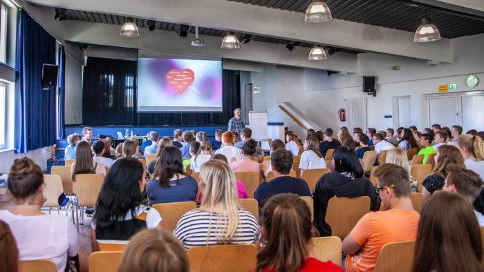 Key Note Speaker und Vortragsredner auf der Bühne und im Vordergrund sind Schüler und Erwachsene